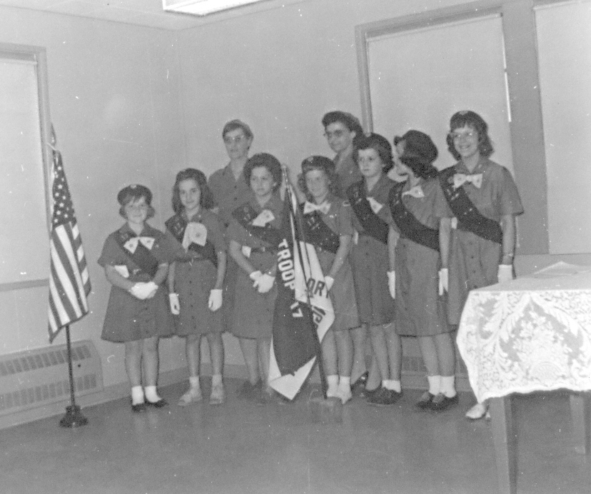 Jane holding flag with Girl Scout Troop in the 1950's
